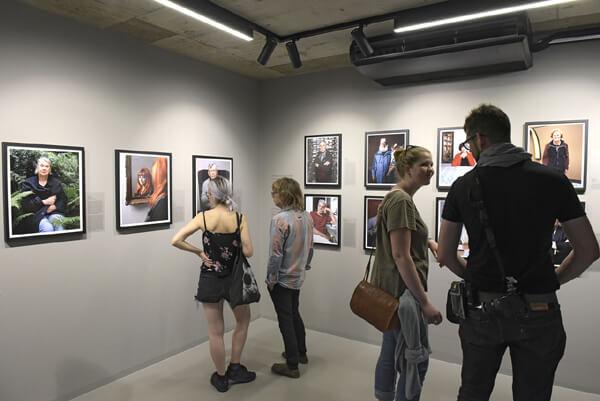 """Besucher betrachten Porträts von """"Im Unruhestand"""""""