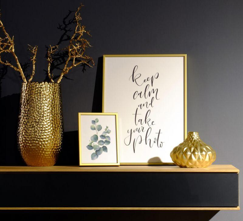 Goldene Bilderrahmen mit Deko auf Sideboard