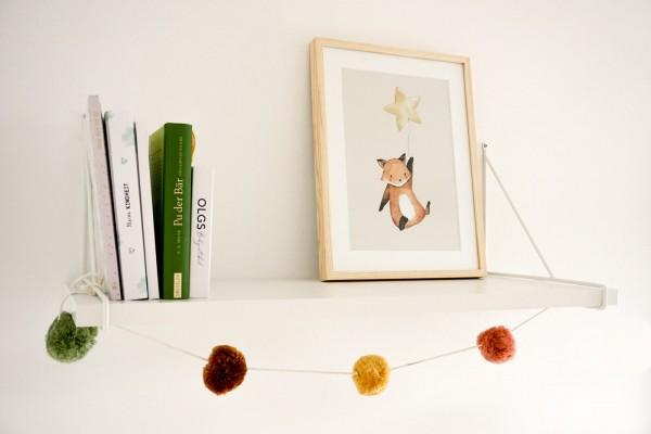 Bilderrahmen im Kinderzimmer auf Regal neben Büchern