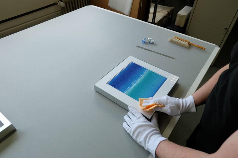 Bilderrahmen-Glas mit Reinigungstuch abwischen