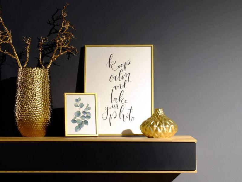 Gold Bilderrahmen auf Sideboard