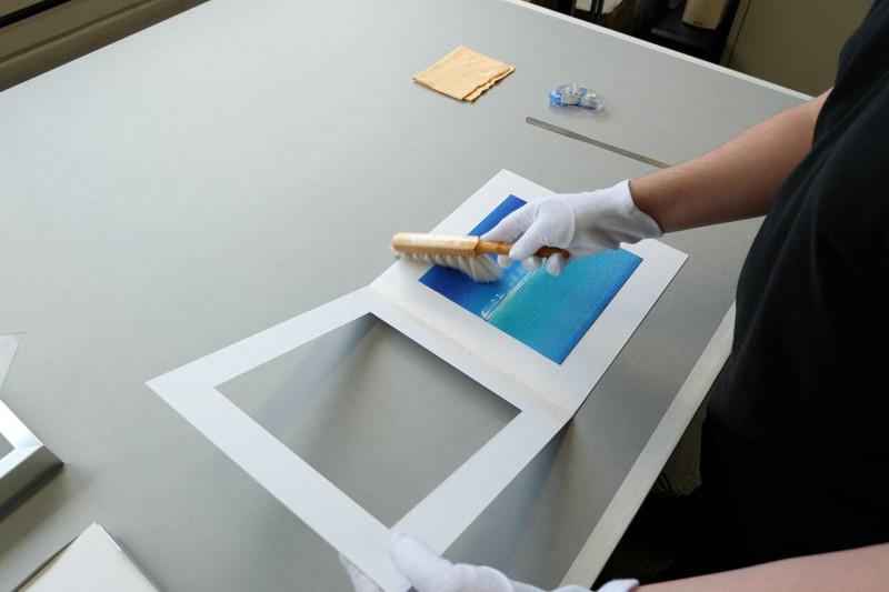 Staub von Bild und Rückwandkarton mit Handbürste entfernen